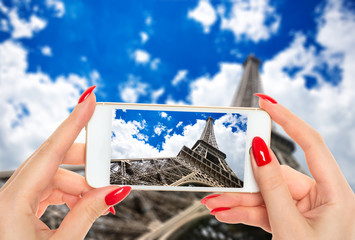 Woman taking a picture of famous Eiffel Tower in Paris