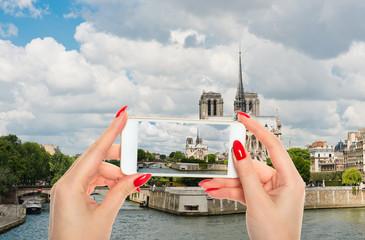Woman taking a picture of Notre Dame de Paris Cathedral.Paris.