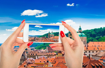 Woman taking a picture of Prague from hill