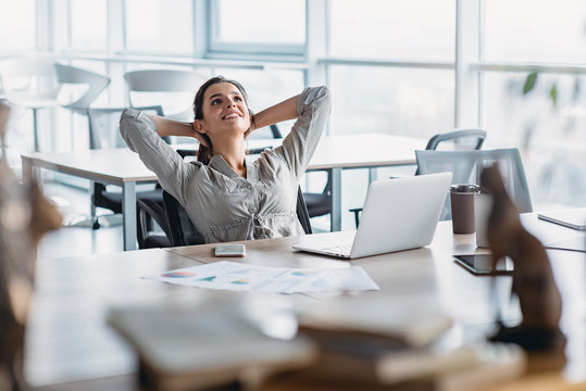 Happy businesswoman relaxing with hands behind head at office desk. Daydreaming concept