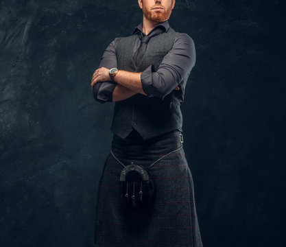 Handsome redhead man dressed in an elegant vest with tie and kilt posing with his arms crossed in studio against a dark textured wall