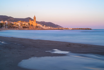 Blue hour view of mediterranean town of Sitges, with the iconic Church of Saint Bartholomew and Santa Tecla, in the suburb area of Barcelona. Blurred sea waves by a slow shutter speed
