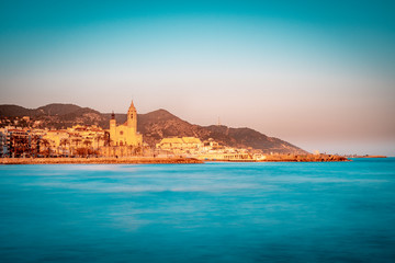 Orange and teal view of mediterranean town of Sitges, with the iconic Church of Saint Bartholomew and Santa Tecla, in the suburb area of Barcelona. Blurred sea waves by a slow shutter speed