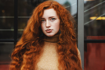 Young redhead lady with natural long curly hair and feckles posing outdoor