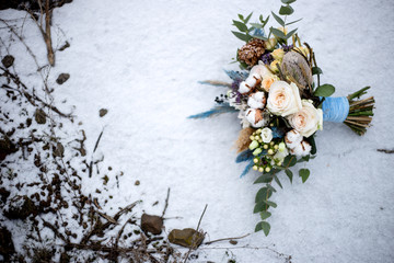 bridal bouquet of white roses and cotton flowers in the snow