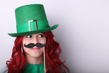 Red hair girl wearing a green Leprechaun's hat and holding a fake moustache