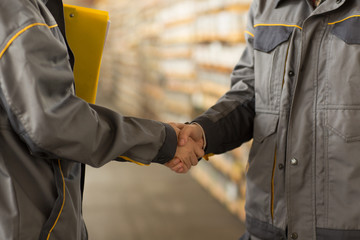 Close up of two female worker shaking hand against warehouse shelves.
