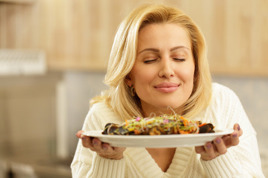 Close up portrait of a gorgeous blond haired mature woman smiling joyfully with her eyes closed, smelling freshly made salad with mussels copy space. Healthy eating, dieting, household concept
