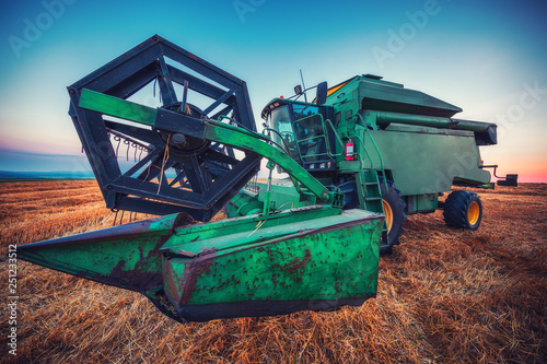 Wall mural Combine harvester machine working in a wheat field at sunset.