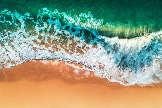 Aerial view of sea waves and sandy beach