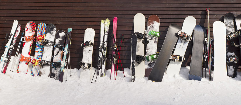 Group of snowboards and skis leaned on wooden wall in ski resort