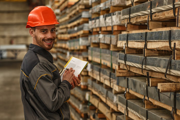 Cheerful warehouse manager wearing hardhat and uniform smiling to the camera while making notes on his clipboard. Wholesale, shipping, logistics concept Wall mural