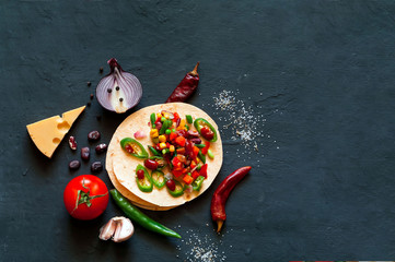 Traditional dish of Mexican cuisine. Corn tortilla tacos with vegetable filling on blue background.