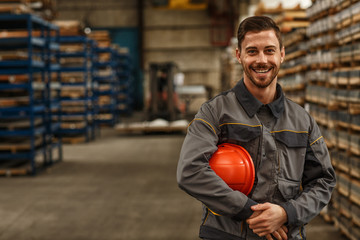 Shot of a handsome young bearded factory worker in uniform holding protective hardhat smiling joyfully to the camera posing at the warehouse of a metalworking company