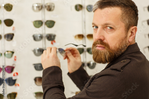 9aa23082302 Close up shot of a bearded man looking seriously to the camera over his  shoulder, while choosing sunglasses at the optometrist shop, copy space.