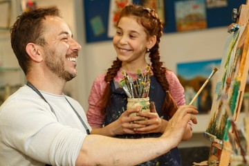 Smiling red haired girl holding brushes for drawing picture by oil, helping her teacher of art and smiling to him. Handsome father and daughter spending time together and having fun in art school.
