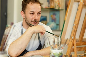 Handsome brunet male artist with bread sitting against picture, touching chin, thinking about creative idea. Painter using oil paints, holding brush in hands. Concept of hobby.