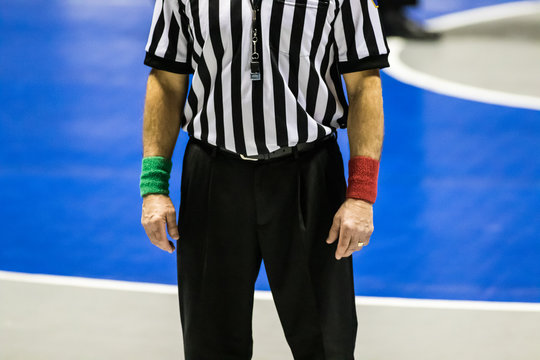 Wrestling referee wearing black pants and black and white stripes on shirt