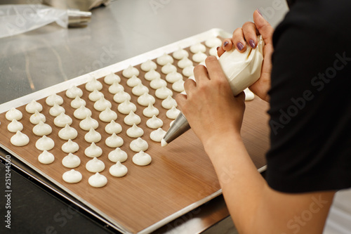Close up of hands of professional confectioner putting white dough