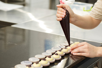 Hands of confectioner cooking macarons. Chef putting chocolate cream on macarons with help of confectionery bag. Concept of confectionery, cuisine and gastronomy.