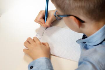 Fototapeta Dłonie chłopca trenującego naukę pisania. Pisanie liter długopisem w zeszycie w kratkę.  obraz