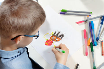 Obraz Chłopiec siedzi przy biurku i rysuje wymyśloną postać na białej kartce papieru. Kolorowe flamastry leżą dookoła na białym blacie. - fototapety do salonu