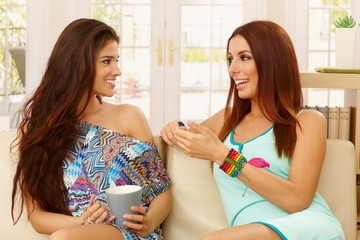 Beautiful girls talking at home on sofa