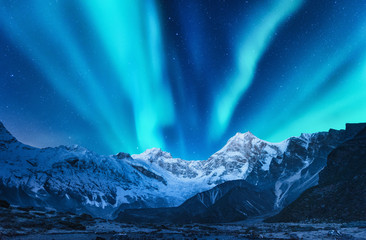 Türaufkleber Nordlicht Aurora borealis above the snow covered mountain range in europe. Northern lights in winter. Night landscape with green polar lights and snowy mountains. Starry sky with aurora over the rocks. Space