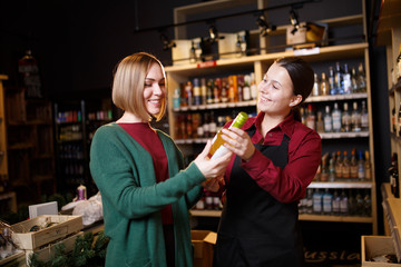 Photo of two women with bottle of wine in hand