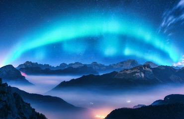Tuinposter Noorderlicht Aurora borealis above mountains in fog at night. Northern lights. Sky with stars with polar lights and high rocks. Beautiful landscape with aurora, city lights in low clouds, mountain ridge. Space