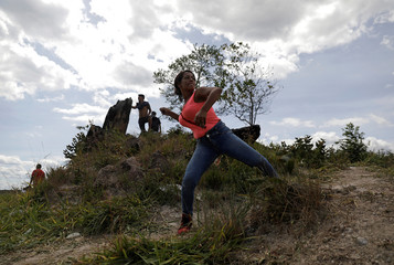 A demonstrator throws a stone at Venezuelan national guards in Pacaraima