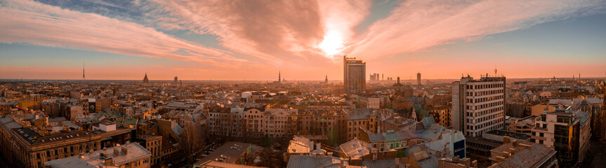 Panorama view of Riga city sunset near the old town including suspension bridge and main cathedral in the city center.