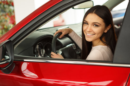 Beautiful young woman sitting in automobile cabin, holding hands on steering wheel, turned, smiling at camera. Pretty female customer of car center doing test drive of new red auto. Transportation.