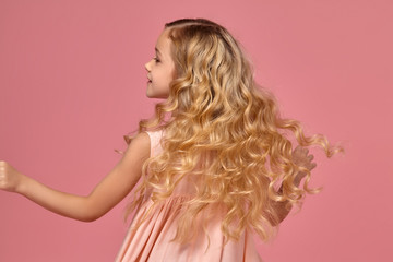 Little girl with a blond curly hair, in a pink dress is posing for the camera