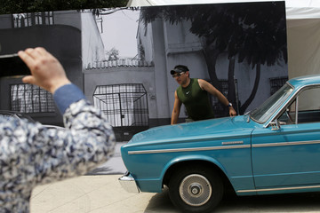 "A man poses for a photo with one of the cars used in the ""Roma"" movie during Roma Fest at Monumento a la Revolucion in Mexico City"
