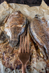Two whole Tilapia baked with spices on wax paper and with fork flat lay
