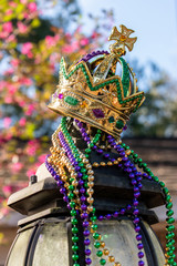 Outdoor Mardi Gras Crown and beads on light post in sunshine