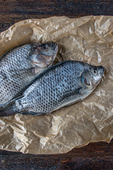 Two whole Tilapia uncooked on wax paper and dark wood background flat lay