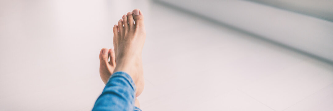 Healthy beautiful feet with pedicure and smooth soft skin of woman barefoot at home - lifestyle banner panorama.