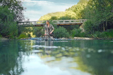 young man in military uniform during world war II is on the river near the old wooden bridge