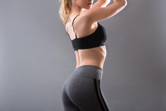 Female sportswear clothes on perfect body. Sport bra and grey leggins pants.