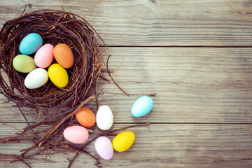 Wall Mural - Colorful Easter eggs in nest on rustic wooden planks background. Holiday in spring season. vintage color tone style. top view composition.