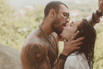 Handsome muscular guy and amazing sexy woman. Cosmopolitan couple. Love and flirt. Muscular man and fit slim young female kissing. Couple goals.