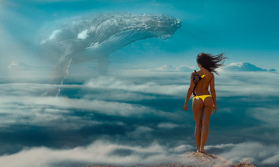 Slender brunette standing on rock against big humpback whale hovering in the sky