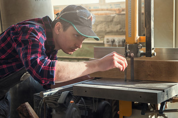 Construction worker cutting wooden board with circular saw