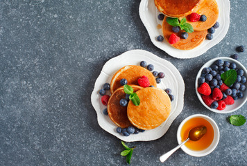 Pancakes with berries and honey, top view, copy space