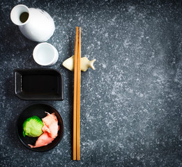 Asian food background with copy space. Sake, chopsticks, wasabi and ginger on dark grey concrete background, flat lay