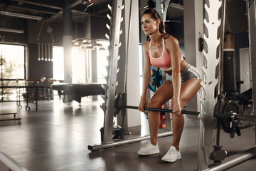 Workout. Athlete woman doing deadlift exercise at gym