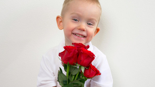 Cute kid ( two years old child)  holding the bouquet of red roses, smiling and looking at camera. Congratulations mother, womens, valentines day concept