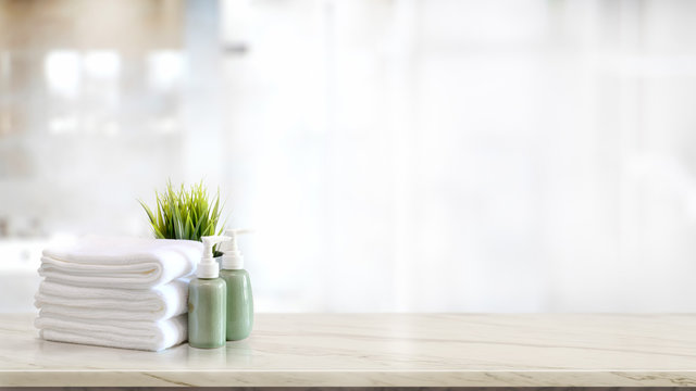 Towels with green ceramics shampoo and soap bottle on marble counter and copy space